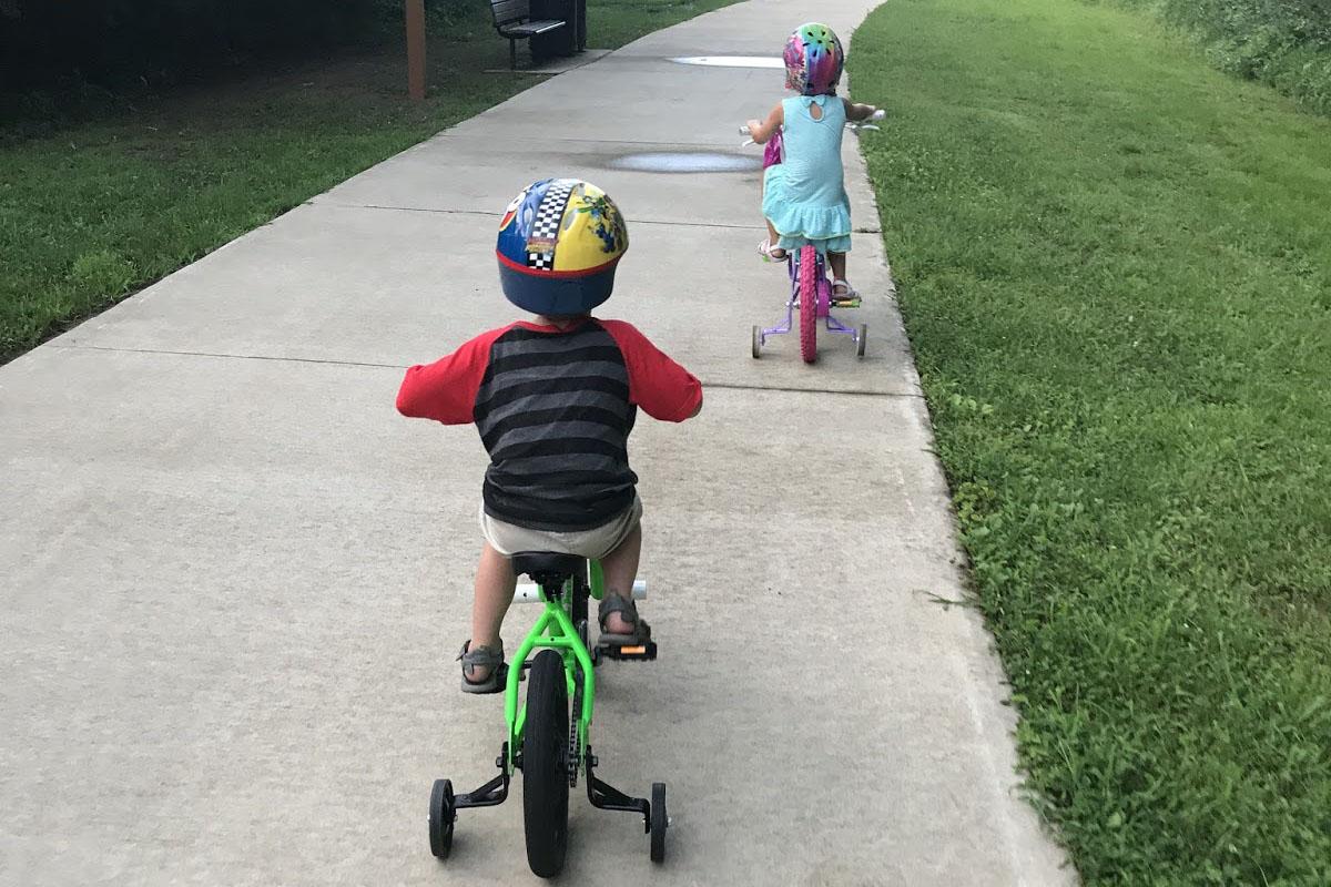 Hai con tập lai xe đạp 3 bánh trẻ em trên đường