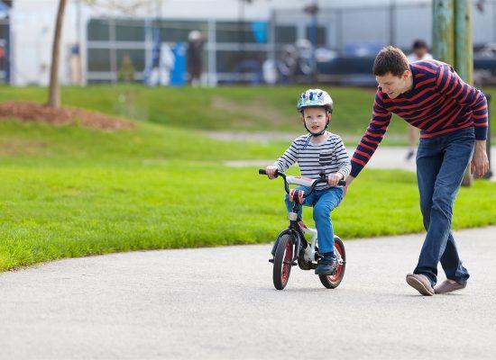 Cha dạy con điều khiển chiếc xe đạp trẻ em