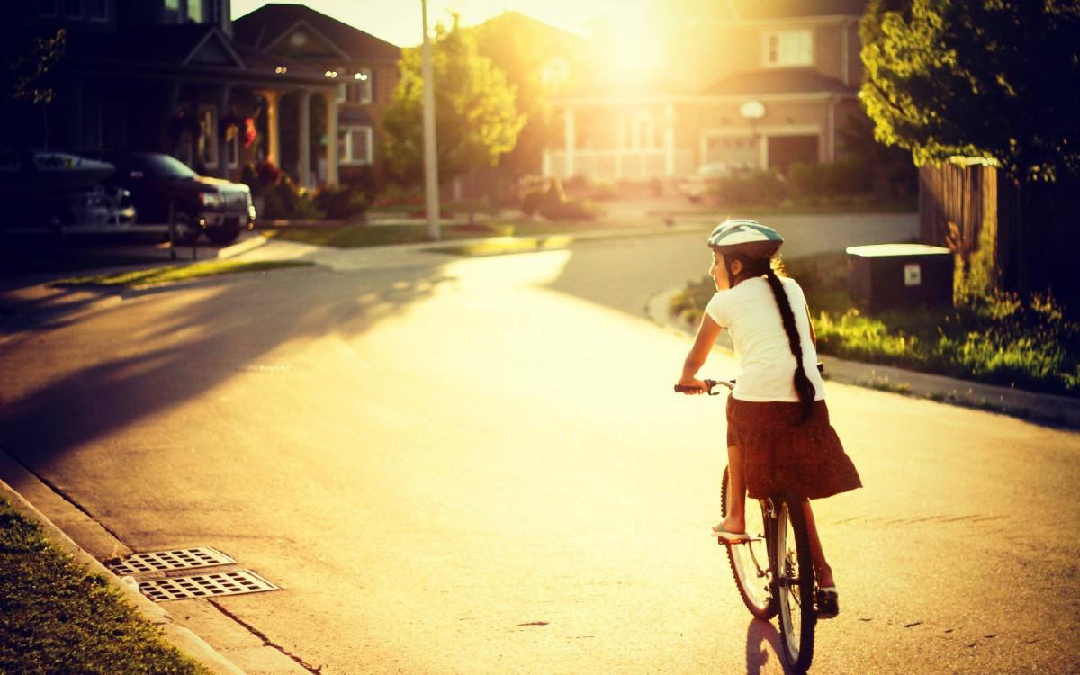Em bé chạy xe đạp đi học dưới nắng hồi