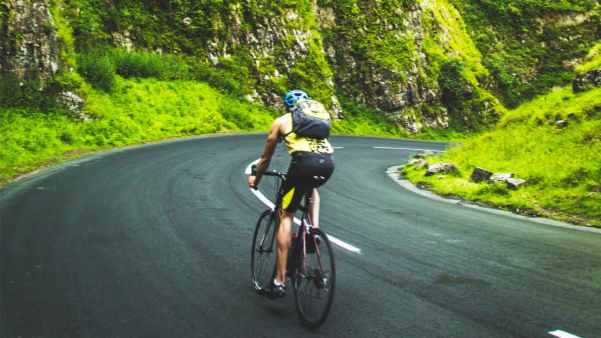 Tay lái trên xe đạp road qua một khúc cua giữa đèo