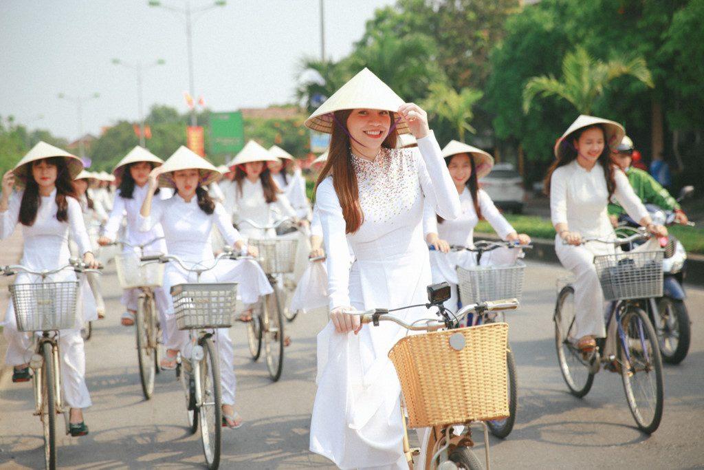 Các bạn nữ đẹp tinh khôi trong tà áo dài trắng đạp xe đạp dành cho học sinh - sinh viên trên đường
