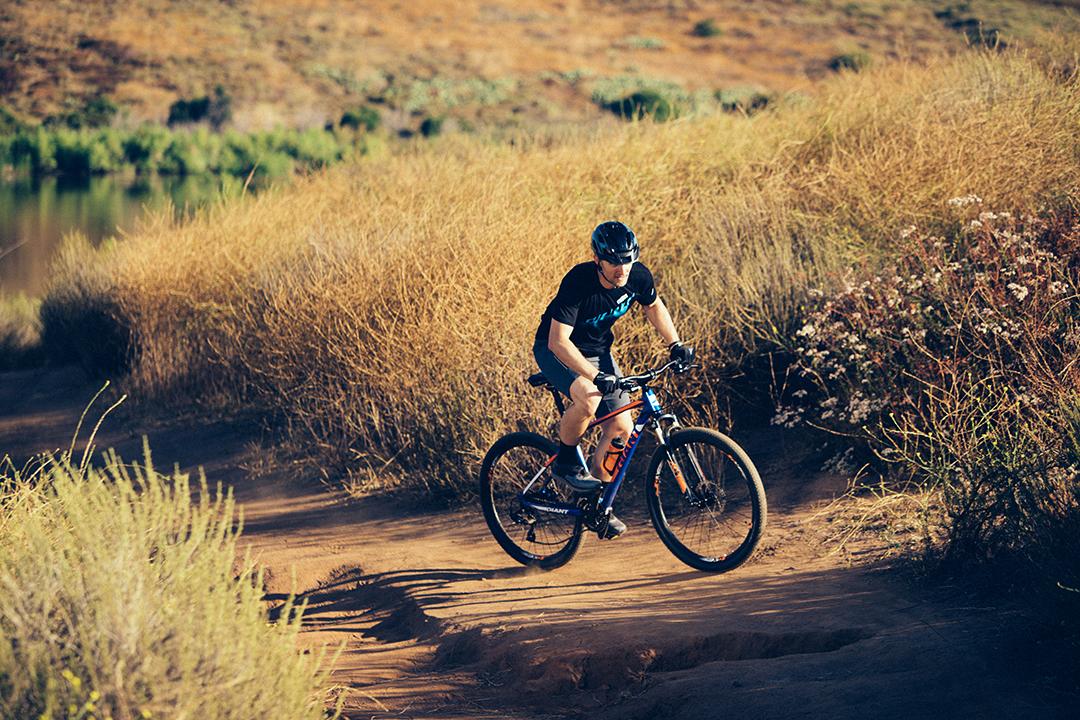 Tay lái đạp đứng trên xe đạp leo núi khi leo dốc