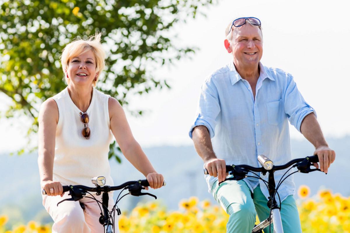 Niềm vui của hai người lớn tuổi khi được đạp xe đạp thể thao dưới nắng sáng