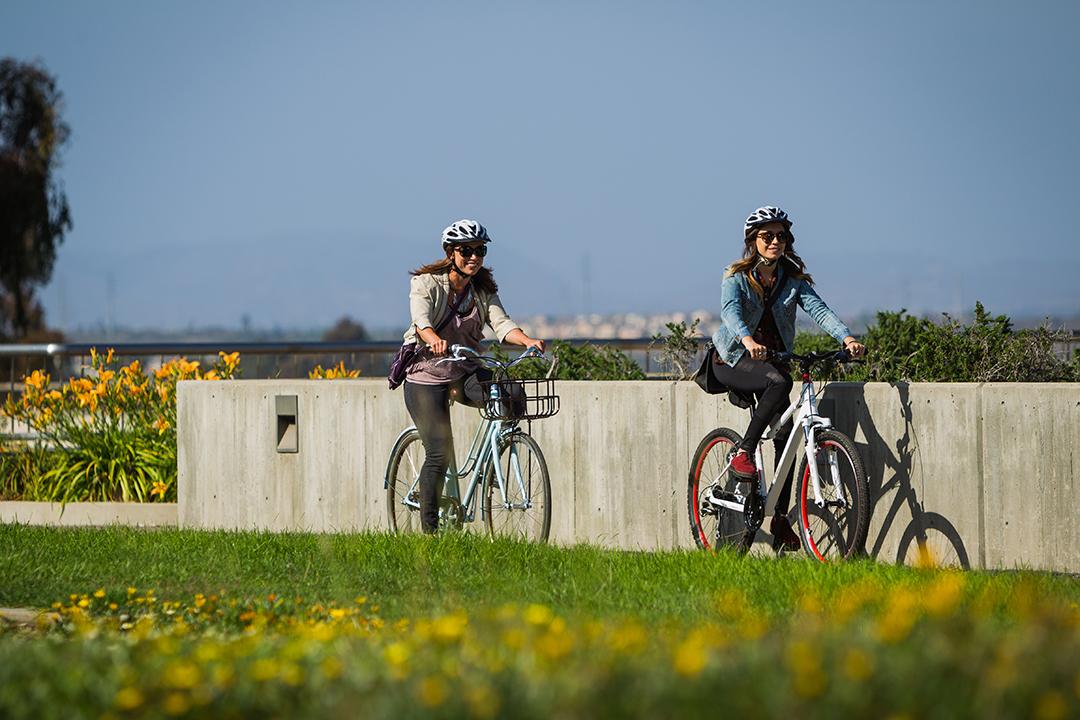Hai bạn học sinh vui tươi trên chiếc xe đạp lúc tan trường