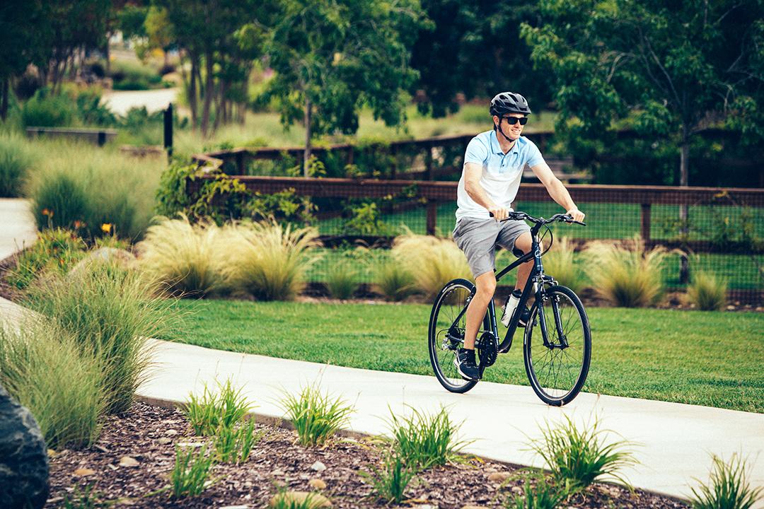 Một người đang sử dụng xe đạp để di chuyển trong thành phố xanh