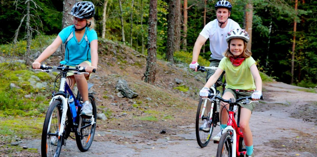 Bố và hai con tập thể dục bằng cách đạp xe trên đường mòn
