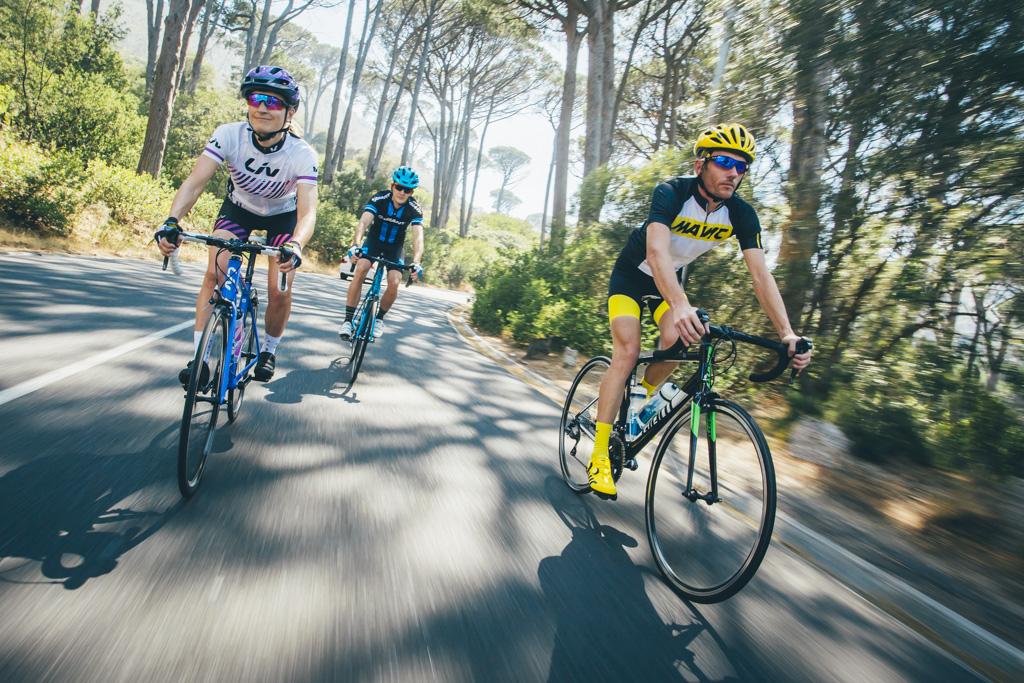 Các tay đua đạp xe dưới hàng cây xanh mát buổi sáng